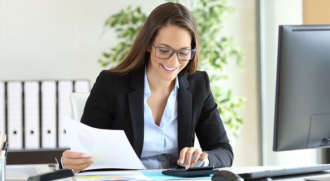 Image of a young business woman using a calculator